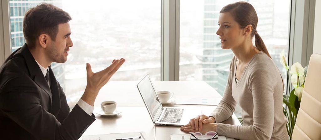 Conversa entre duas pessoas, uma está indicando algum gesto.