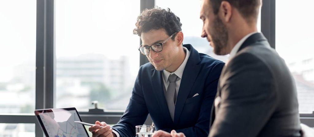 Reunião entre dois homens, um está apontando para um gráfico no tablet.