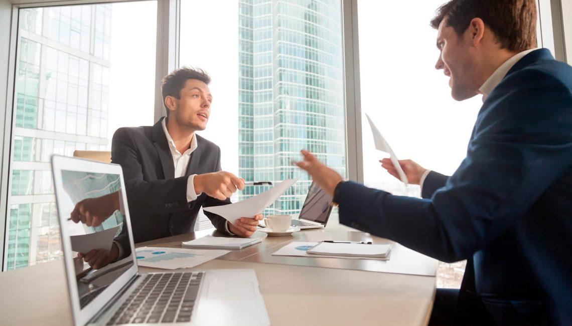 Conversa entre dois homens em uma mesa de escritório.
