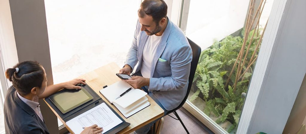Conversa sobre planejamento tributário entre duas pessoas que estão em uma mesa cheia de livros.