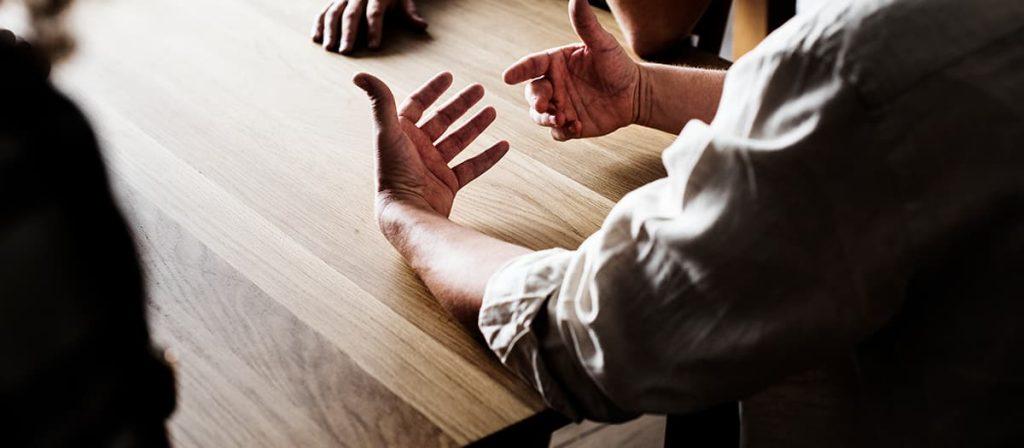 Conversa entre várias pessoas em uma de reunião.