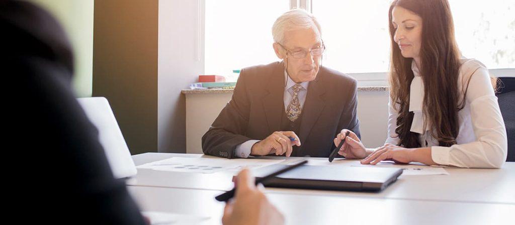 Conversa entre duas pessoas em uma mesa de escritório.