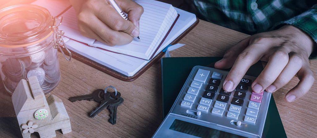 Homem em uma mesa de escritório usando uma calculadora e escrevendo em um caderno.