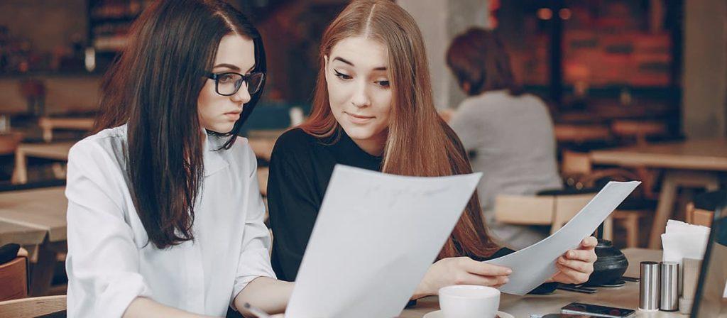 Duas mulheres conversando, ambas estão com uma folha na mão.