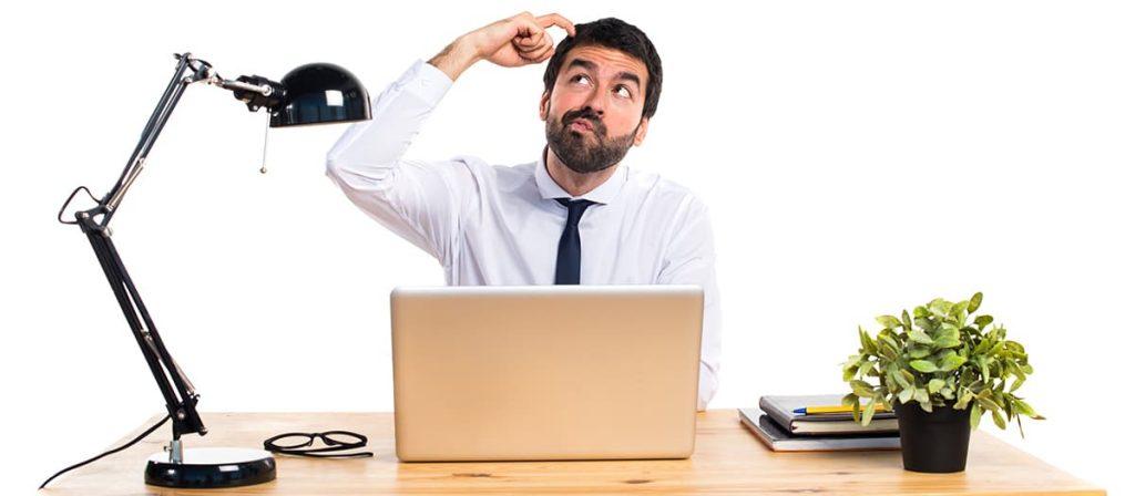 Homem pensativo em uma mesa de escritório.