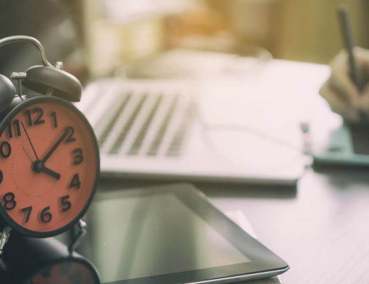 Mesa de escritório com vários itens como relogio, notebook.