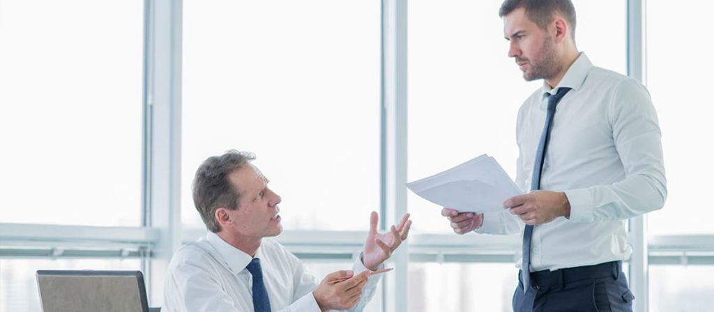 Conversa entre dois homens, um está com umas folhas na mão, o outro está com a cara fechada.