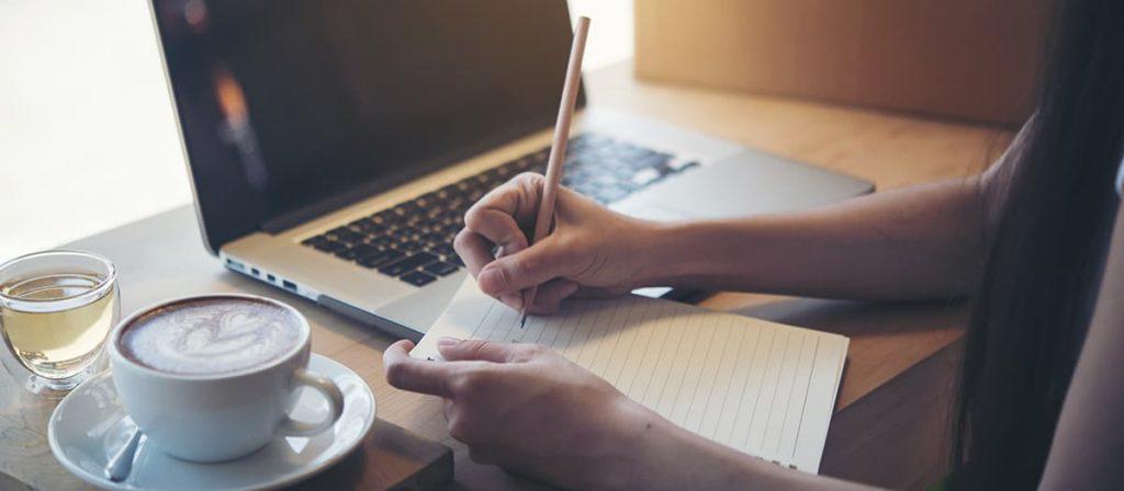 Pessoa escrevendo em um caderno, ao lado tem um café e um notebook.