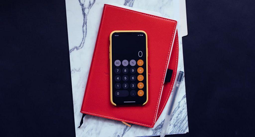 Uma calculadora sobre uma agenda vermelha.