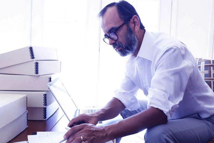 Homem de barba fazendo contas em um caderno com uma pilha de arquivos e um laptop ao lado.