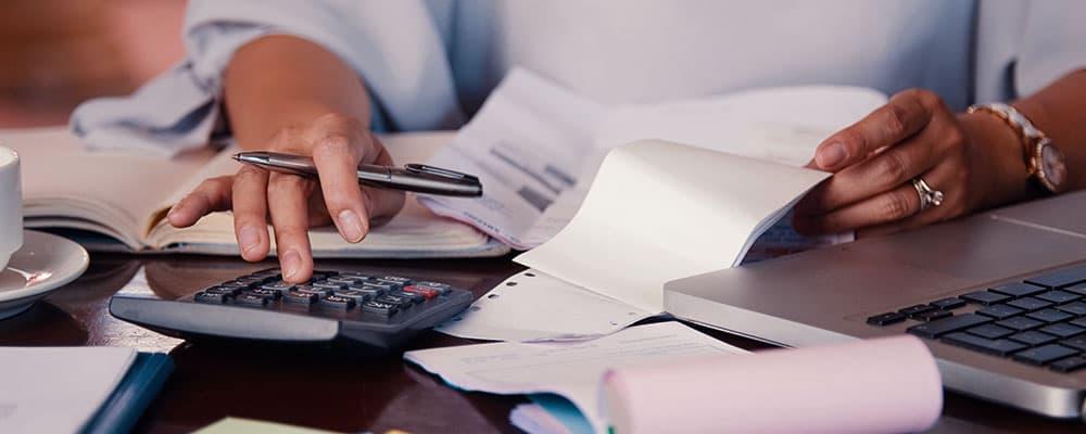 Pessoa fazendo contas em uma calculadora.