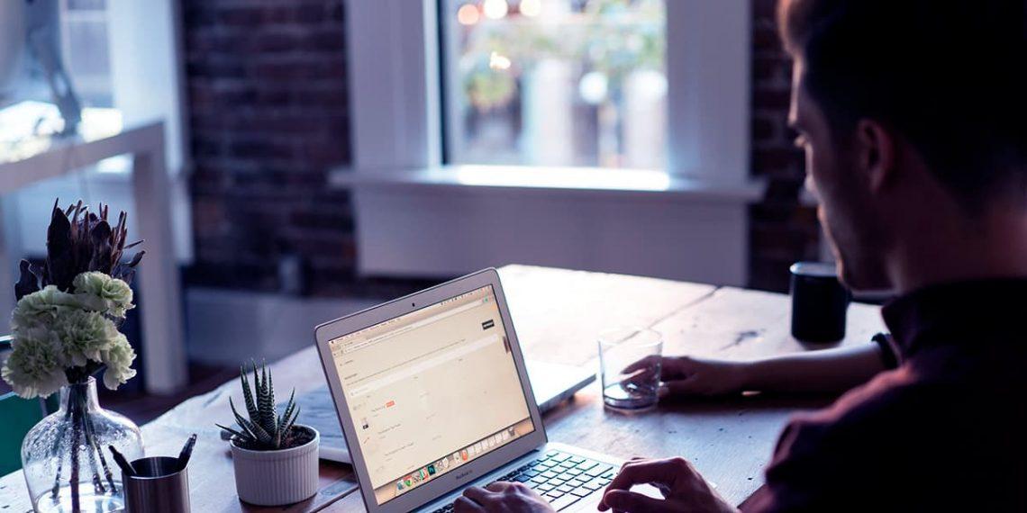 Homem usando seu notebook em sua mesa de trabalho.
