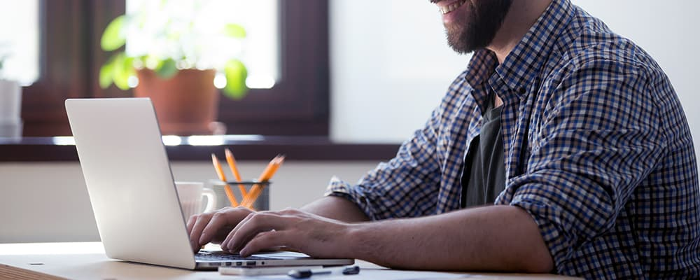 Homem trabalhando em seu notebook.