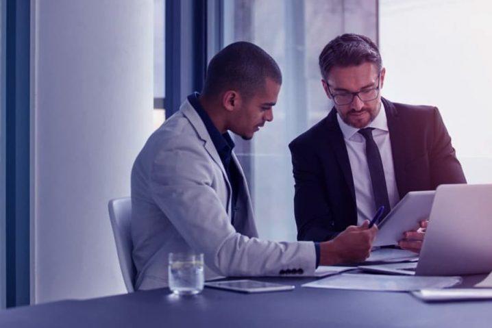 Um homem negro trocando ideias com seu funcionário sobre o planejamento de sua sociedade.
