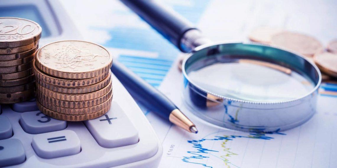 Lupa, caneta, moedas e uma calculadora para descrever sonegação fiscal.