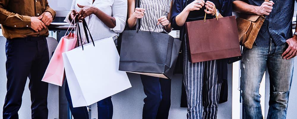 Várias pessoas segurando várias sacolas com compras.