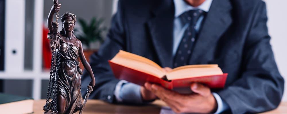 Foto de um advogado trabalhando com um livro aberto.