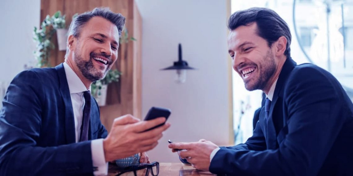 Dois homens de negócio trocando ideias ao olhar um telefone celular.