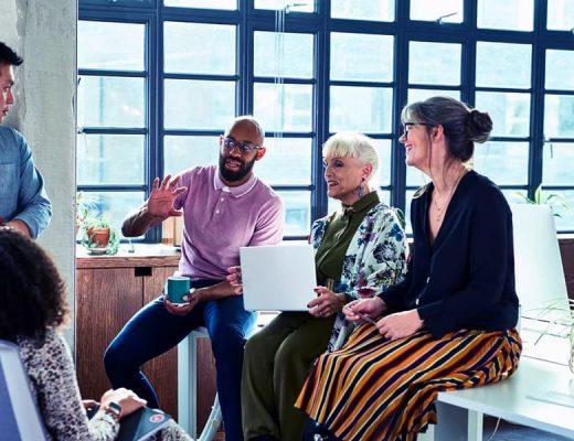 Grupo de seis pessoas trocando ideias no ambiente de trabalho.