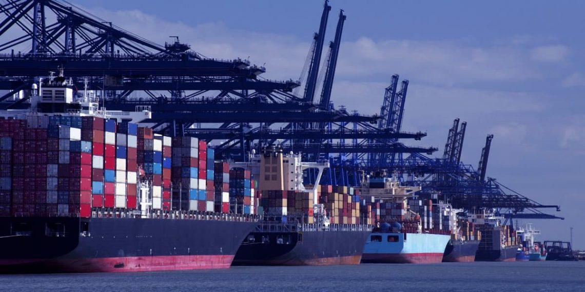 Um porto com navios atracados e guindastes para contêineres.