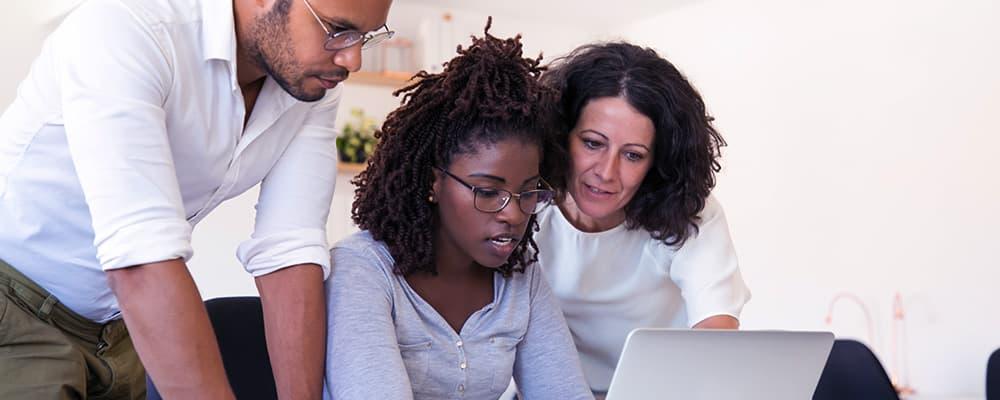 3 pessoas fazendo uma reunião com sua chefe negra.